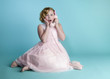 Cute little girl talking on a vintage pink telephone