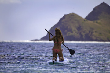young japanese woman in a bikini with her paddle board