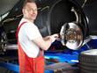 Motorcar mechanic fixing the break of a car in a garage