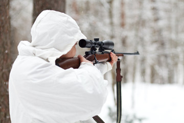 Soldier in white camouflage aiming with sniper rifle at winter f