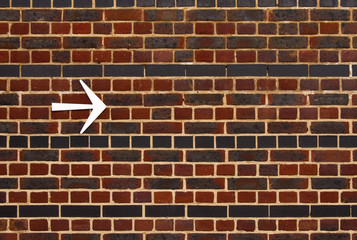 Bright arrow pointing the right direction on a brick wall