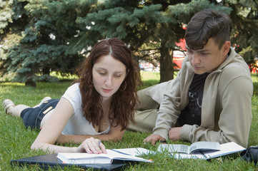 two student  studying outdoors on grass