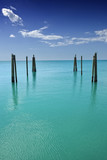 Mooring posts leading in turquoise sea in Governor's Harbour - Fine Art prints