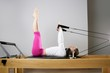 gym woman pilates stretching sport in reformer bed
