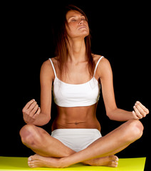 young woman in lingerie meditating, black background