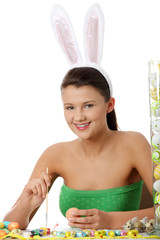 Young girl with bunny ears is making easter decoration