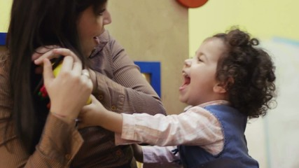 teacher and baby girl playing with toy at preschool