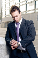 Worried businessman checking time