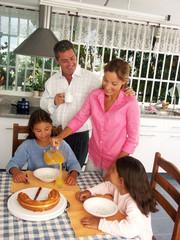 Familia desayunando en la cocina.