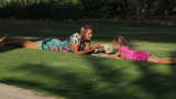 Girl draws on the lawn with his mother