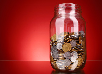 coins in money jar on red background. Ukrainian coins