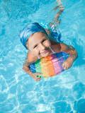 Fototapety Little girl swimming in blue water