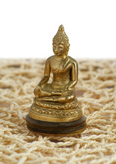 Bronze Buddha in a lotus position on the mat