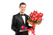 Handsome male holding a bouquet of flowers and gift