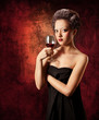 Woman with glass of red wine on grunge background