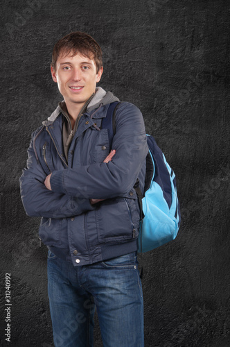 A man stands with a backpack on his shoulder