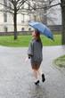 junge Frau läuft lachend durch den Regen