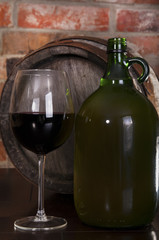 Glass,barrel and a bottle of wine to stand near a brick wall. In