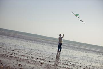 A senior woman flying a kite on the beach