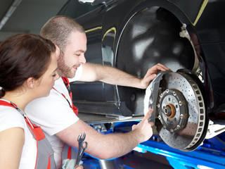 Apprentice is learning to fix a brake of a car