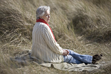 A senior woman sitting amongst the sand dunes