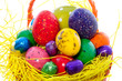 colorful painted and edible easter eggs in a wicker orange baske
