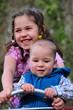 Baby mit Schwester auf der Wippe