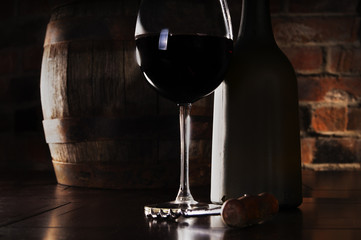 Glass, barrel and a bottle of red wine to stand near a brick wal