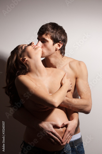 Handsome man kissing pregnant woman