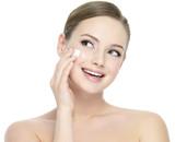 Happy woman applying cosmetic cream