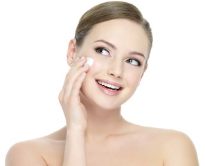 Happy woman applying cosmetic cream