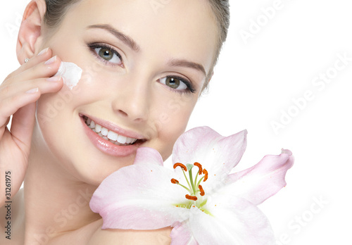 Happy smiling girl with lily applying cream
