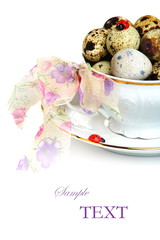 Easter eggs in a teacup on a white background.