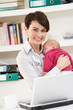 Woman With Newborn Baby Working From Home Using Laptop