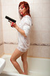 sexy young red-haired woman in shower with gun