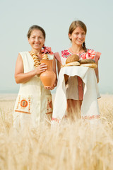 Women with bread at cereals field
