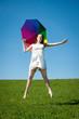 Fröhliche junge Frau springt mit Schirm auf einer Wiese