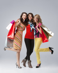 studio image three beautiful young women holding shopping bags s