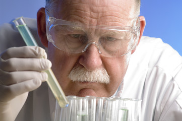 Scientist working with chemicals on blue background