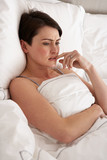 Worried Woman Laying Awake In Bed