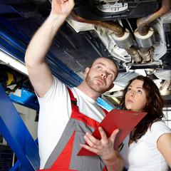 Motorcar mechanic explaining the engine damage to a customer