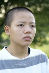 Depressed asian teen girl with shaved bald head