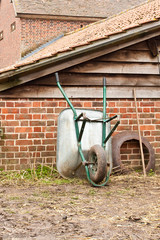 Wheelbarrow upturned in a yard