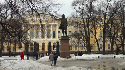 People walk near the monument To Pushkin
