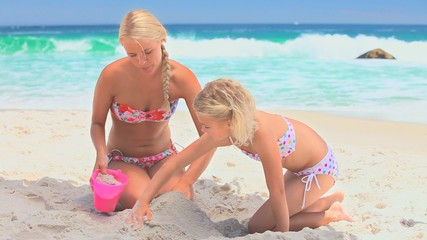 Woman and daughter making sand castles