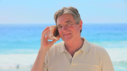 Mature man listening to a shell