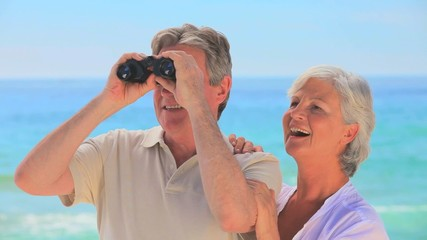 Elderly couple using binoculars