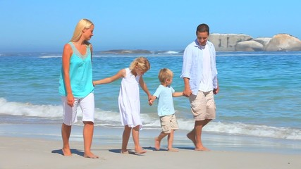 Cute family walking on a beach