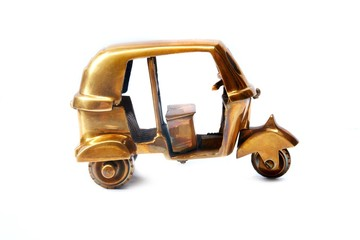 Golden rickshaw souvenir over white background