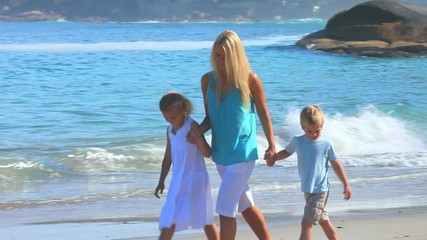 Blonde woman on a beach with her children